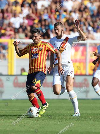 Lecce's Filippo Falco (L) and Roma's Edin Dzeko (R) in action during the Italian Serie A soccer match US Lecce vs AS Roma at the Via del Mare stadium in Lecce, Italy, 29 September 2019.