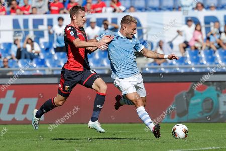Genoa's Lukas Lerager, left, and Lazio's Ciro Immobile vie for the ball during a Serie A soccer match between Lazio and Genoa, at the Rome Olympic Stadium