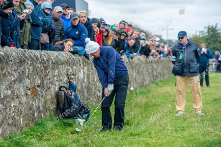 Gerry McIlroy, father of Rory McIlroy, plays his shot from near to the wall on the 16th green during the final round of the Alfred Dunhill Links Championship European Tour at St Andrews, West Sands