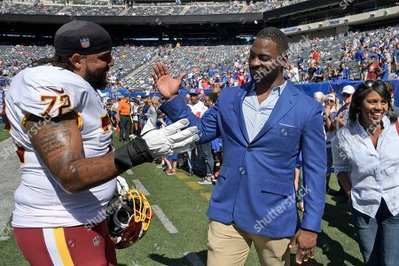 Former New York Giants Justin Tuck, right, greets Washington Redskins' Donald Penn before an NFL football game, in East Rutherford, N.J