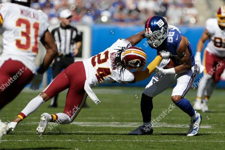 Washington Redskins' Josh Norman (24), left tries to tackle New York Giants' Darius Slayton during the first half of an NFL football game, in East Rutherford, N.J