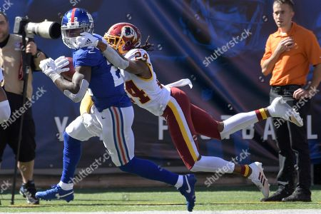 Washington Redskins' Josh Norman, right, tries to stop New York Giants' Wayne Gallman during the first half of an NFL football game, in East Rutherford, N.J