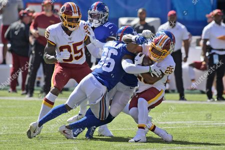 Washington Redskins' Chris Thompson, right is tackled by New York Giants defense during the first half of an NFL football game, in East Rutherford, N.J