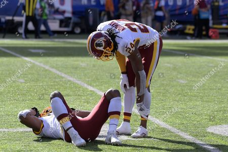 Washington Redskins' Josh Norman, right, stands over Fabian Moreau after he was hurt on the play during the second half of an NFL football game against the New York Giants, in East Rutherford, N.J