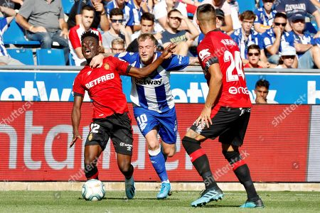 Stock Image of Deportivo Alaves'  John Guidetti (C) duels for the the ball with RCD Mallorca's Iddrisu Mohammed (L) and Martin Valjent (R) during the Spanish LaLiga soccer match played at the Mendizorroza stadium in Vitoria, northern Spain, 29 September 2019.