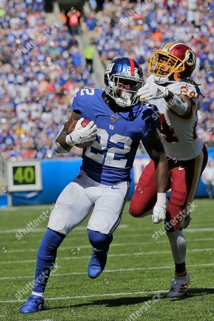 Washington Redskins' Josh Norman, right, tries to grab New York Giants running back Wayne Gallman during the first half of an NFL football game, in East Rutherford, N.J