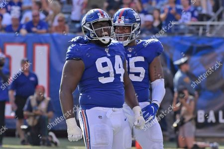 New York Giants' Dalvin Tomlinson, left, and B.J. Hill celebrates after a sack during the second half of an NFL football game against the Washington Redskins, in East Rutherford, N.J