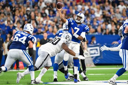 Stock Image of Indianapolis Colts quarterback Jacoby Brissett (7) throws as he's hit by Oakland Raiders defensive tackle Johnathan Hankins (90) during the first half of an NFL football game in Indianapolis