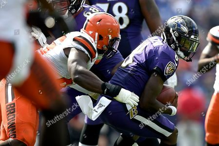 Baltimore Ravens quarterback Lamar Jackson, right, is tackled by Cleveland Browns defensive tackle Larry Ogunjobi during the second half of an NFL football game, in Baltimore