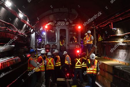 MTA workers inside the L train subway tunnel.