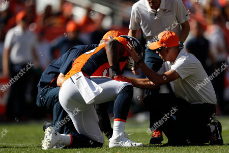 Stock Image of IDenver Broncos linebacker Corey Nelson is helped by trainers after an injury during the first half of an NFL football game against the Jacksonville Jaguars, in Denver
