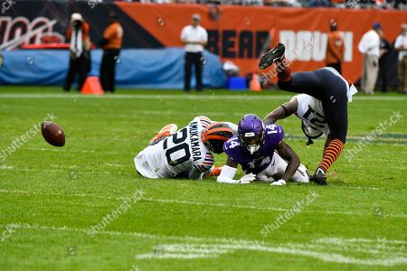 Minnesota Vikings wide receiver Stefon Diggs (14) fumbles after being hit by Chicago Bears cornerback Prince Amukamara (20). during the first half of an NFL football game, in Chicago. The Bears recovered the fumble