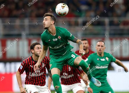 Fiorentina's Gaetano Castrovilli controls the ball in the air ahead of AC Milan's Davide Calabria, left, during a Serie A soccer match between AC Milan and Fiorentina, at the San Siro stadium in Milan, Italy