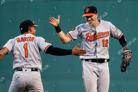 Stock Photo of Stevie Wilkerson, Richie Martin. Baltimore Orioles' Stevie Wilkerson (12) celebrates with Richie Martin (1) after making the catch on a flyout by Boston Red Sox's Jackie Bradley Jr. during the eighth inning of a baseball game in Boston