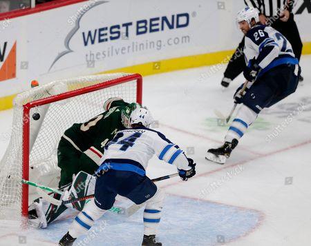 Winnipeg Jets defenseman Josh Morrissey (44) scores the game winning goal past Minnesota Wild goalie Devan Dubnyk (40) on an assist from Winnipeg Jets forward Blake Wheeler (26) in overtime of an NHL hockey game in St. Paul, Minn. The Jets defeated the Wild 5-4
