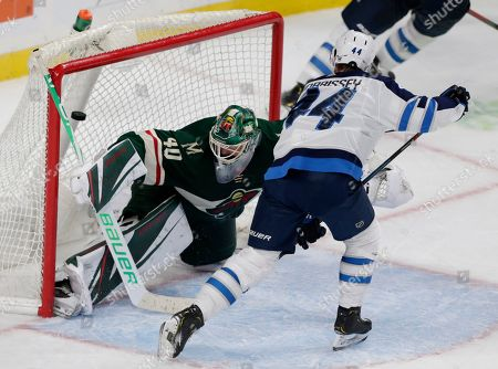 Winnipeg Jets defenseman Josh Morrissey (44) scores the game winning goal past Minnesota Wild goalie Devan Dubnyk (40) in overtime of an NHL hockey game in St. Paul, Minn. The Jets defeated the Wild 5-4