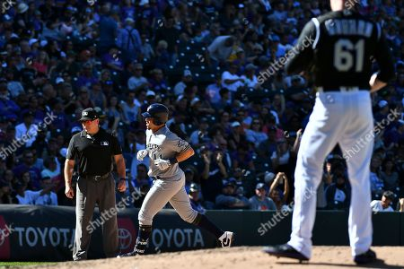 Milwaukee Brewers' Hernan Perez (14) rounds third base after his home run in the sixth inning off of Colorado Rockies relief pitcher Sam Howard (61) during a baseball game, in Denver
