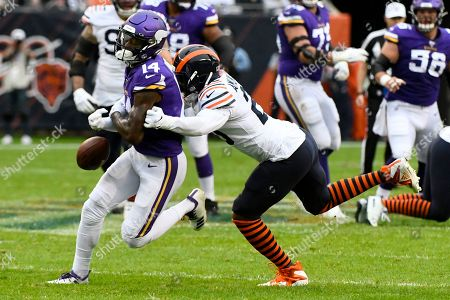 Minnesota Vikings wide receiver Stefon Diggs, left, fumbles as he is hit by Chicago Bears cornerback Prince Amukamara during the first half of an NFL football game, in Chicago. The Bears recovered the fumble