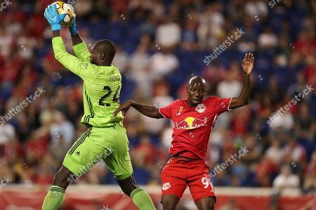 D.C. United goalkeeper Bill Hamid (24) jumps up to catch the ball while New York Red Bulls forward Bradley Wright-Phillips (99) attempts to attack during the second half of an MLS soccer match, in Harrison, N.J. The match ended in a 0-0 draw