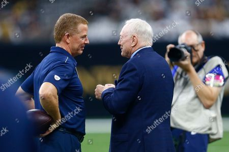 Dallas Cowboys owner Jerry Jones, left, and head coach Jason Garrett talk on the field before an NFL football game against the New Orleans Saints in New Orleans