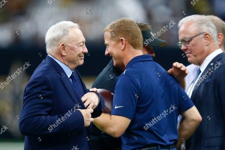 Dallas Cowboys owner Jerry Jones, left, and head coach Jason Garrett walk on the field before an NFL football game against the New Orleans Saints in New Orleans