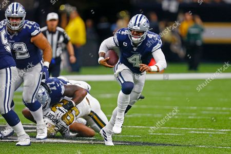 Dallas Cowboys quarterback Dak Prescott (4) scrambles as New Orleans Saints defensive end Marcus Davenport (92) is shoved to the turf by Cowboys offensive tackle Tyron Smith (77) in the first half of an NFL football game in New Orleans