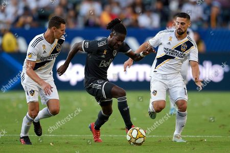 Tosaint Ricketts, Daniel Steres, Sebastian Lletget. Vancouver Whitecaps FC forward Tosaint Ricketts moves the ball between LA Galaxy defender Daniel Steres and midfielder Sebastian Lletget during the second half of an MLS soccer match in Carson, Calif., . The Whitecaps won 4-3