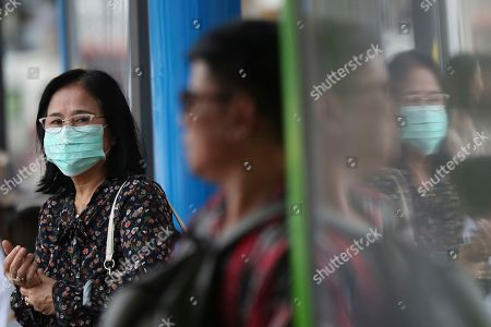A pedestrian wears a face mask to filter dirty air, an action suggested by Prime Minister Prayuth Chan-ocha, in Bangkok, Thailand, . Many provinces of Thailand, including Bangkok, are shrouded with toxic smog Monday, causing concerns among people of much worst situation in the upcoming dry season when agriculture burning season really begins