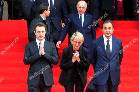 Martin Rey-Chirac, left, Claude Chirac, center, son and daughter of former President Jacques Chirac, and Claude's husband Frédéric Salat-Baroux, right, are applauded as they leave Saint Sulpice Church in Paris, where past and current heads of states gathered to pay tribute to Chirac who died last week at the age of 86