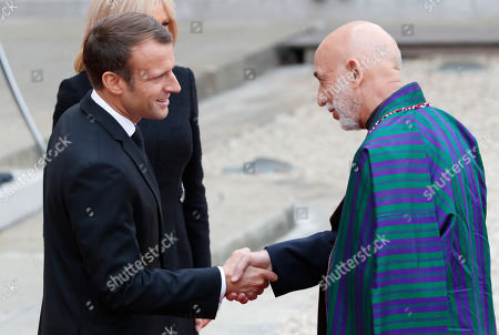 Former Afghan President Hamid Karzai, right, is greeted by French President Emmanuel Macron and his wife Brigitte when arriving at Elysee palace in Paris, after paying tribute to former French President Jacques Chirac who died last week at the age of 86