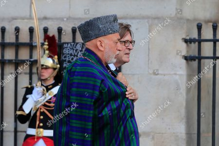 Former Afghan President Hamid Karzai and former Belgian Prime Minsiter Guy Verhofstadt, rear, arrive at Saint Sulpice church in Paris, . Past and current heads of states are gathering in Paris to pay tribute to former French president Jacques Chirac. A private family church service for Chirac, who died last week at the age of 86, is taking place Monday