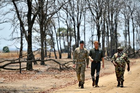 Britain's Prince Harry, with Brigadier Tom Bateman, left, arrives at the memorial site for Guardsman Mathew Talbot of the Coldstream Guards at the Liwonde National Park in Malawi, on day eight of the royal tour of Africa. Guardsman Talbot lost his life in May 2019 on a joint anti-poaching patrol with local park rangers