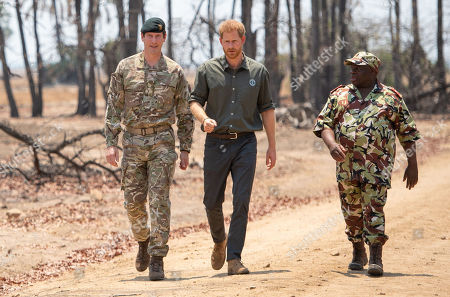 Stock Photo of Prince Harry, with Brigadier Tom Bateman (left), arrives at the memorial site for Guardsman Mathew Talbot of the Coldstream Guards at the Liwonde National Park in Malawi, on day eight of the royal tour of Africa. Guardsman Talbot lost his life in May 2019 on a joint anti-poaching patrol with local park rangers.
