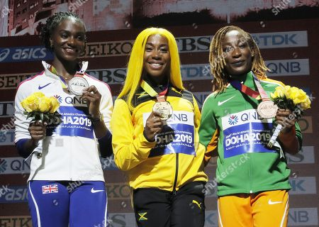 Stock Picture of Gold medalist Shelly-Ann Fraser-Pryce (C) of Jamaica, silver medalist Dina Asher-Smith (L) of Great Britain and bronze medalist Marie-Josee Ta Lou of Ivory Coast during the medal ceremony for the Women's 100m at the IAAF World Athletics Championships 2019 at the Khalifa Stadium in Doha, Qatar, 30 September 2019.