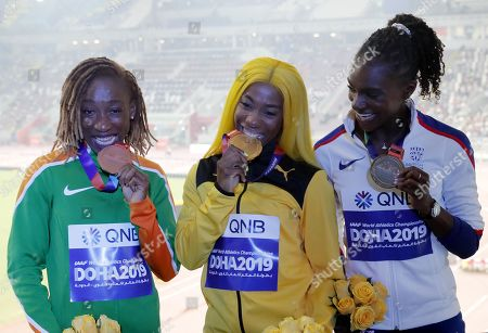Gold medalist Shelly-Ann Fraser-Pryce (C) of Jamaica, silver medalist Dina Asher-Smith (R) of Great Britain and bronze medalist Marie-Josee Ta Lou of Ivory Coast during the medal ceremony for the Women's 100m at the IAAF World Athletics Championships 2019 at the Khalifa Stadium in Doha, Qatar, 30 September 2019.