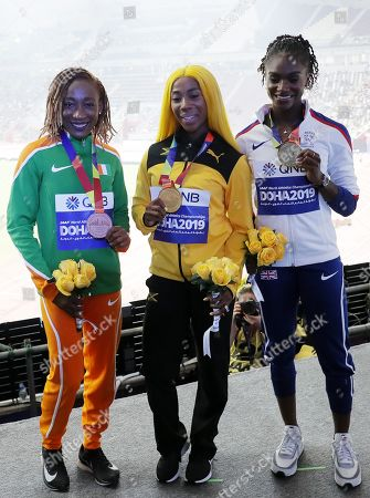 Stock Photo of Gold medalist Shelly-Ann Fraser-Pryce (C) of Jamaica, silver medalist Dina Asher-Smith (R) of Great Britain and bronze medalist Marie-Josee Ta Lou of Ivory Coast during the medal ceremony for the Women's 100m at the IAAF World Athletics Championships 2019 at the Khalifa Stadium in Doha, Qatar, 30 September 2019.