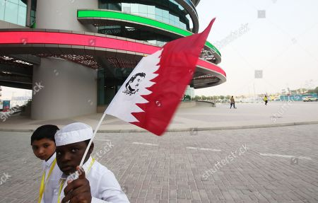 Children carrying the Qatari flag with the picture Qatari Emir Sheikh Tamim bin Hamad Al Thani as they arrive to the Khalifa Stadium for the fourth day of the IAAF World Athletics Championships 2019 in Doha, Qatar, 30 September 2019.