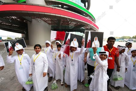 Children carrying the Qatari flag and pictures of Qatari Emir Sheikh Tamim bin Hamad Al Thani as they arrive to the Khalifa Stadium for the fourth day of the IAAF World Athletics Championships 2019 in Doha, Qatar, 30 September 2019.