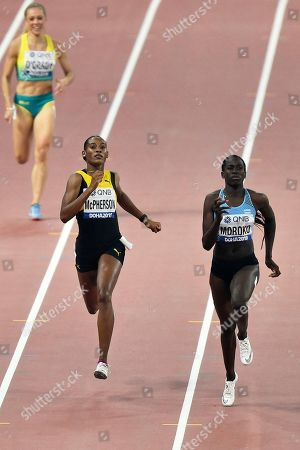 Stephenie Ann McPherson, of Jamaica, and Galefele Moroko, of Botswana, right, compete in the women's 400 meter heats during the World Athletics Championships in Doha, Qatar