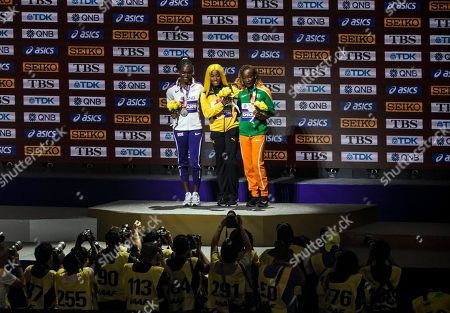 Shelly-Ann Fraser-Pryce of Jamaica, gold, Dina Asher-Smith of Great Britain, silver, and Marie-Josee Ta Lou of The Ivory Coast, bronze, during the medal ceremony the women's 100 meters at the World Athletics Championships in Doha, Qatar