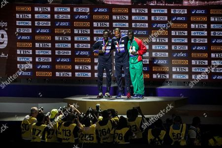 Christian Taylor of the United States, gold, Will Claye of the United States, silver, and Hugues Fabrice Zango of Burkina Faso, bronze, during the medal ceremony for the men's triple jump at the World Athletics Championships in Doha, Qatar