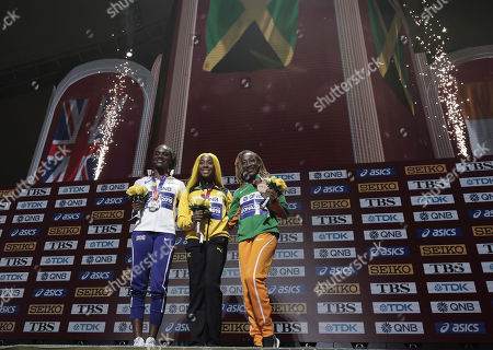Shelly-Ann Fraser-Pryce of Jamaica, center, gold, Dina Asher-Smith of Great Britain, left, silver, and Marie-Josee Ta Lou of The Ivory Coast, bronze, during the medal ceremony the women's 100 meters at the World Athletics Championships in Doha, Qatar