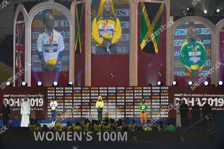 Shelly-Ann Fraser-Pryce of Jamaica, center, gold, Dina Asher-Smith of Great Britain, left, silver, and Marie-Josee Ta Lou of The Ivory Coast, bronze, during the medal ceremony for the women's 100 meters at the World Athletics Championships in Doha, Qatar