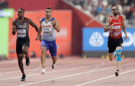 Aaron Brown, of Canada, left, Adam Gemili, of Great Britain and Ramil Guliyev, of Turkey, compete in a men's 200 meter semifinal at the World Athletics Championships in Doha, Qatar
