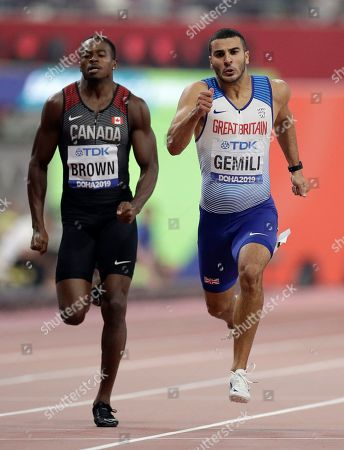 Aaron Brown, of Canada, left, and Adam Gemili, of Great Britain compete in a men's 200 meter semifinal at the World Athletics Championships in Doha, Qatar