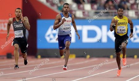 Andre De Grasse, of Canada, left, Zharnel Hughes, of Great Britain and Yohan Blake, of Jamaica, compete in a men's 200 meter semifinal at the World Athletics Championships in Doha, Qatar
