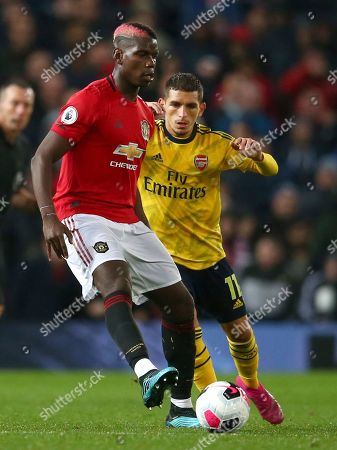 Manchester United's Paul Pogba, left, vies for the ball with Arsenal's Lucas Torreira during the English Premier League soccer match between Manchester United and Arsenal at Old Trafford in Manchester, England