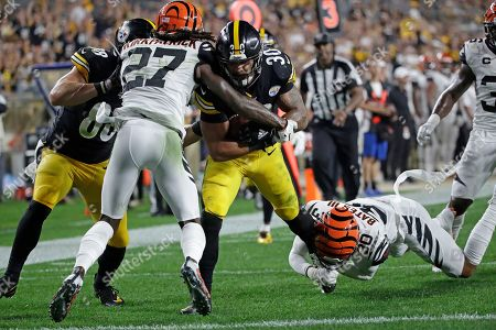 Stock Picture of Pittsburgh Steelers running back James Conner (30) scores with Cincinnati Bengals free safety Jessie Bates (30) and cornerback Dre Kirkpatrick (27) defending during the first half of an NFL football game in Pittsburgh