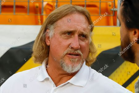 Stock Image of Pro Football Hall of Fame outside linebacker Kevin Greene stands on the sidelines during warmups before an NFL football game between the Pittsburgh Steelers and the Cincinnati Bengals in Pittsburgh