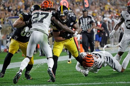 Pittsburgh Steelers running back James Conner (30) scores with Cincinnati Bengals free safety Jessie Bates (30) and cornerback Dre Kirkpatrick (27) defending during the first half of an NFL football game in Pittsburgh